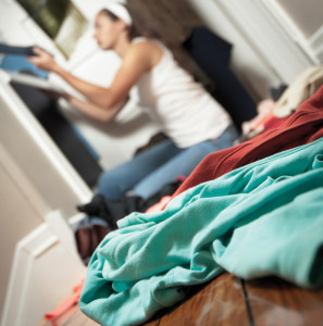 Young woman cleaning out her closet